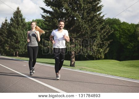 Fitness, sport, friendship and lifestyle concept - smiling couple running outdoors. Man and woman training after hard-working day.