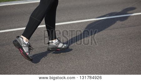 Jogging woman on track. Legs of woman running on road near park or forest. Closeup of female in running shoes going for run on road at sunrise or sunset.