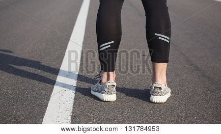 Closeup of male in running shoes going for run on road at sunrise or sunset. Man's legs in jogging shoes on road near park.