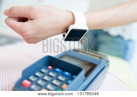 Customer paying with NFC technology with wearable watch