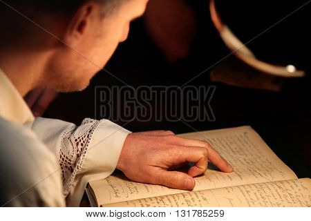 A young priest reading an ancient hand written document