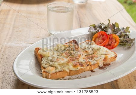 Pizza ToastGlass of water placed on wooden table.