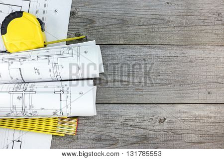 Rolls Of Architectural Blueprints And Measurement Tools On Gray Wooden Background