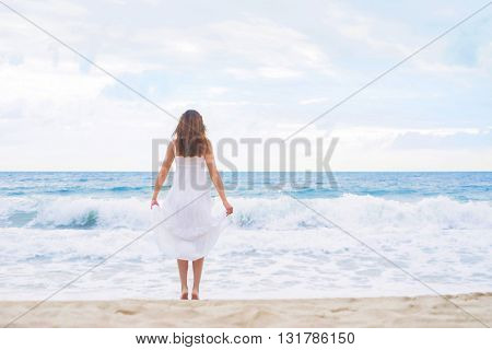 Beautiful brunette going to the wavy ocean holding her white dress.