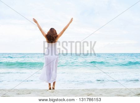 Rear view of attractive, young woman with hands up in the air while walking towards the ocean.