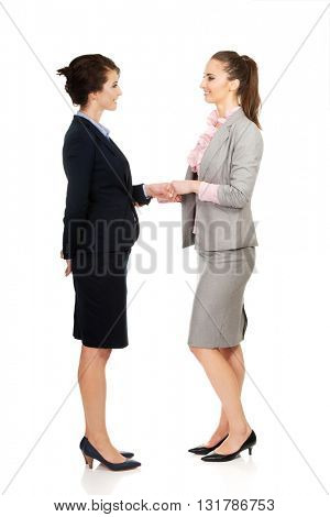 Two women in office outfits giving handshake.