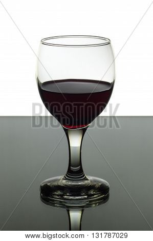 A glass of red wine on black and white background with a beautiful light.