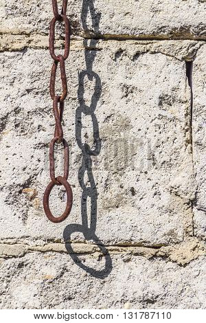 Old rusty chain hanging on a stone wall background