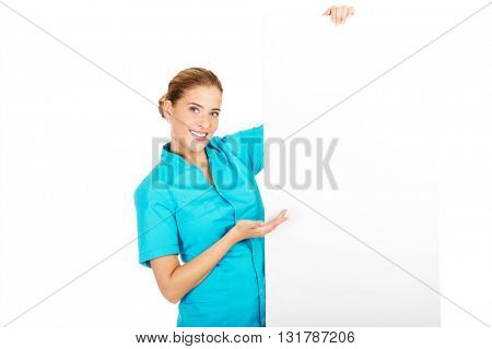 Young female doctor or nurse holding empty banner