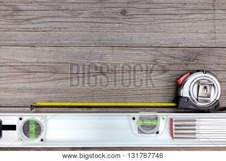 tape measure and spirit level on gray wooden boards