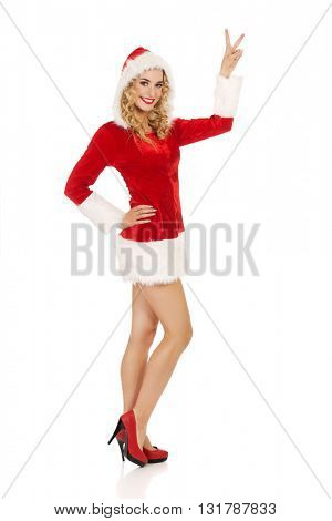 Young santa woman shows victory sign