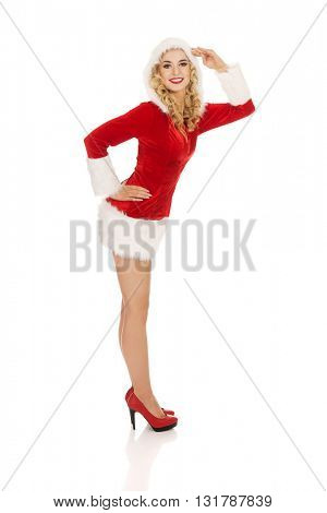 Young beautiful santa woman salutes