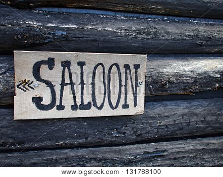Wild west American saloon sign hanged on a wooden house