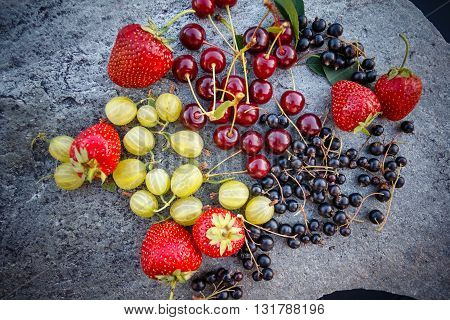 Mix of fresh and juicy cherries black currant strawberries and gooseberries in the summer garden on a grey stone