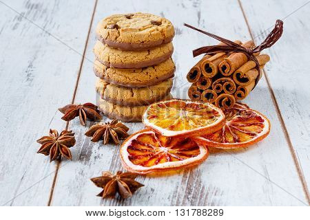 Chocolate cookies with dry oranges anise and cinnamon on the light wooden boards