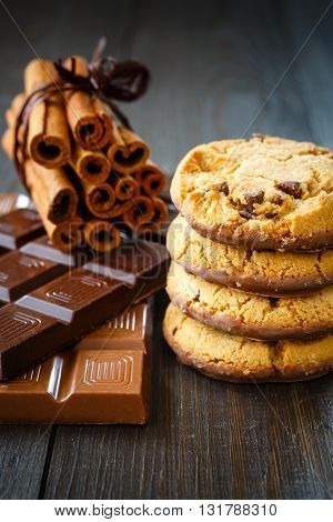 Chocolate cookies stacked vertical milk and dark chocolate bar and cinnamon on rustic wooden background.