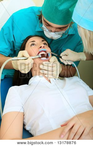 Shot of a young woman with dentist in a dental surgery. Healthcare, medicine.