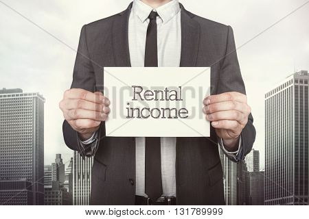 Rental income on paper what businessman is holding on cityscape background