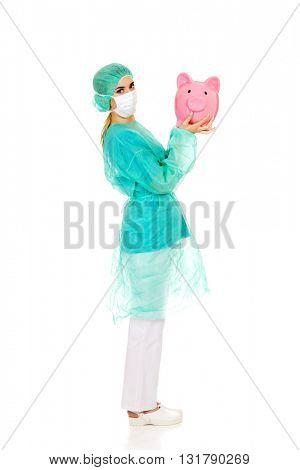 Female surgeon doctor holding piggy bank