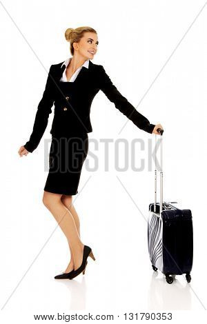 Smile businesswoman dragging wheeled suitcase