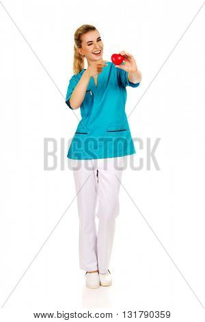 Smiling nurse or female doctor with heart