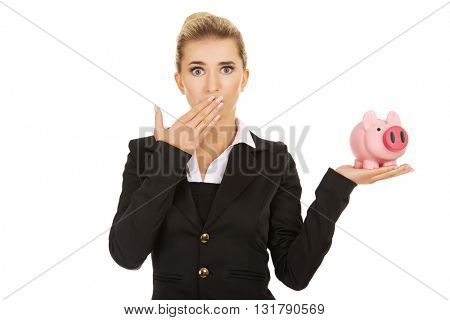 Surprised businesswoman holding a piggybank