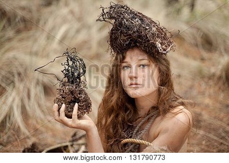 Conceptual portrait of young woman holding seaweed and wearing a seaweed crown