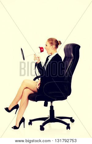 Business woman sitting on armchair and screaming through a megaphone