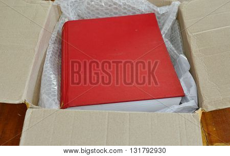 red book with air bubble in brown paper box
