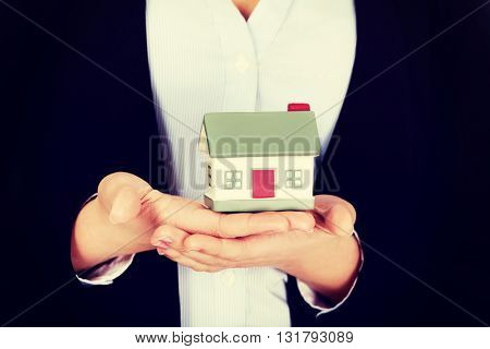 Business woman holding a house model