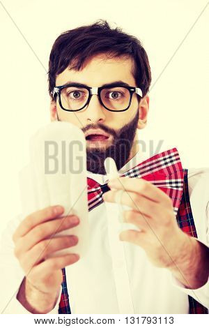 Shocked man holding menstruation pad.