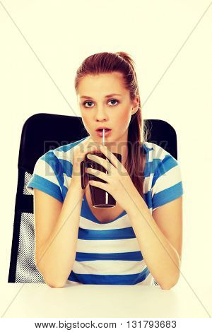 Teenage woman drinking something through straw