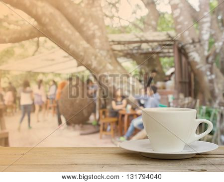 Vintage tonecoffee cup on wood table with Coffee shop blur background