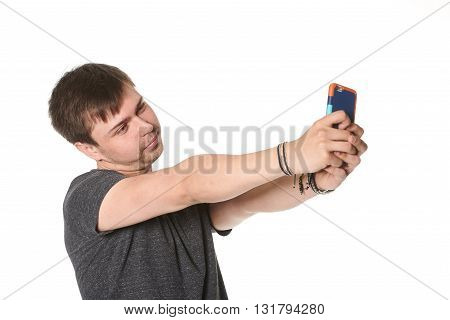 Casual young man taking selfie on mobile phone isolated on white