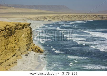 sea waves on shore of pacific ocean with yellow rocks in desert in peru