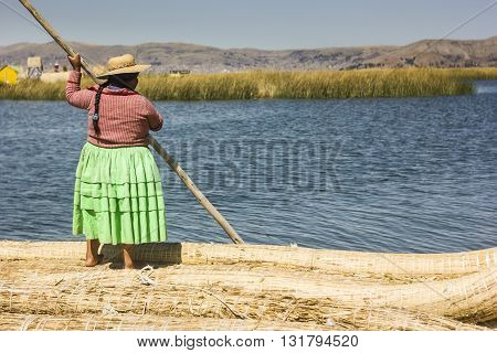 fat peruvian woman in traditional dress standing with stick on boat ot titicaca lake