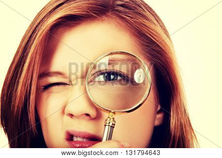 Teenage woman looking through a magnifier