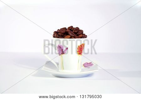 roasted coffee beans in porcelain cup on a background