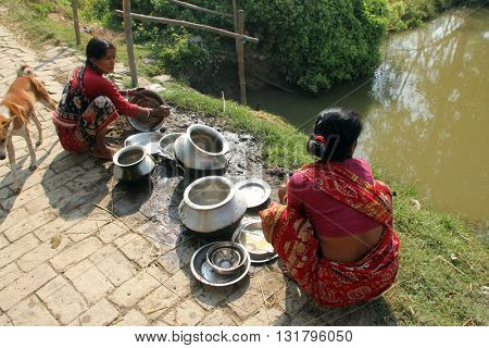 BAIDYAPUR, INDIA - DECEMBER 02: Woman washes dishes in Baidyapur, West Bengal, India on December 02, 2012.