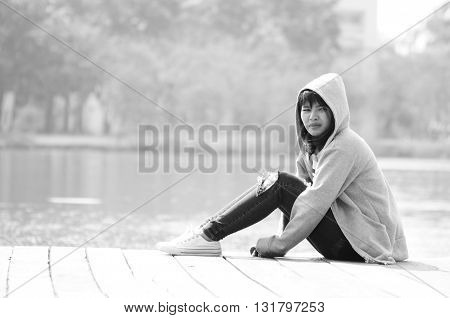 Sad woman waiting and sitting near river