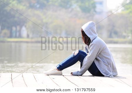Upset and depressed woman sitting Near River