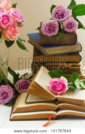 Pile of old books with bouqet of pink and violet rose flowers