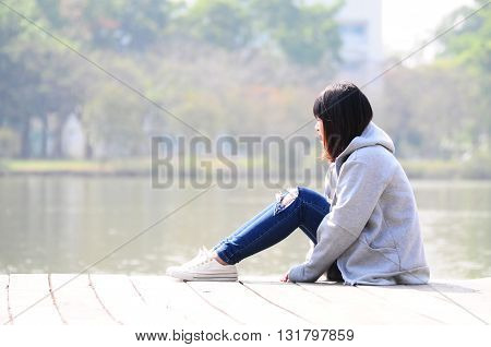 Upset woman is sitting near the river