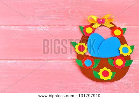 Easter basket with eggs and flowers made of cardboard, on pink wooden background. Homemade Easter basket idea.  Easter background