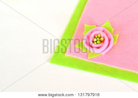 Pink flower with green leaf on a color felt and white wooden background. Original wool felt flower