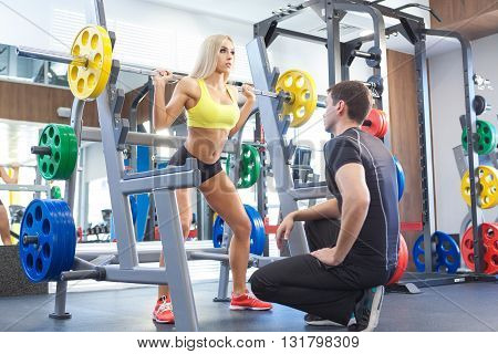 man and woman with barbell flexing muscles in gym. woman and personal trainer in gym