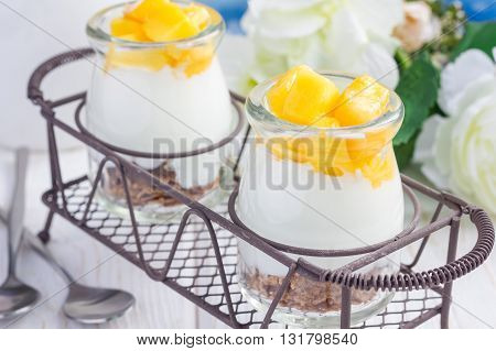 Breakfast dessert with bran flakes plain yogurt and mango in iron tray closeup