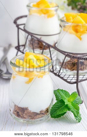 Breakfast dessert with bran flakes plain yogurt and mango in iron tray