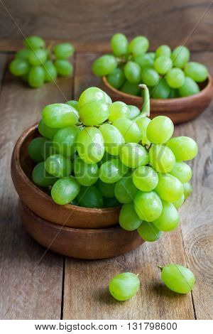 Bunch of green ripe grapes in a wooden bowl on rustic wood background