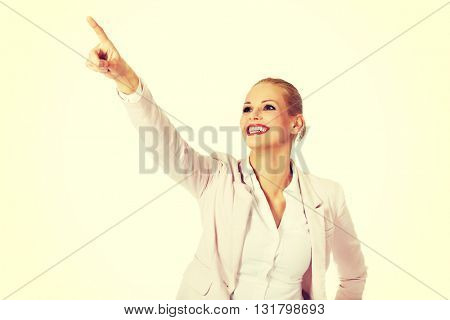 Young smiling business woman pointing for copyspace or something